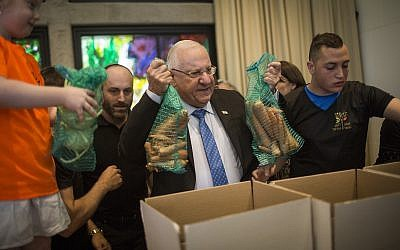 President Reuven RIvlin helps volunteers pack boxes with food for needy families ahead of Passover, at the President's Residence in Jerusalem, on April 19, 2016. (Hadas Parush/Flash90/File)