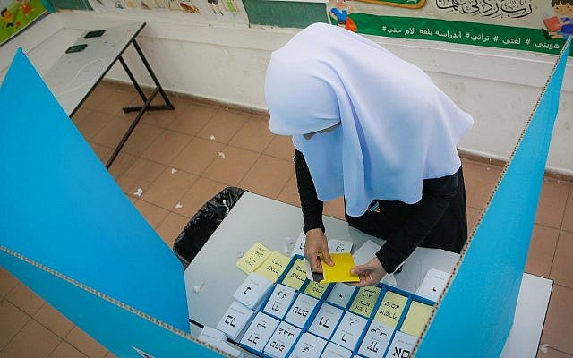 Illustrative: An Arab Israeli woman casts her ballot at a voting station in municipal elections on October 30, 2018, in Kafr Kasm. (Roy Alima/Flash90)