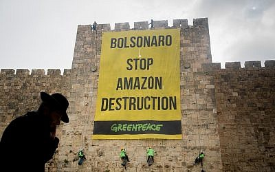 Greenpeace activists rappel down the walls of the Jerusalem's Old City, during a protest on April 1, 2019, to hang a banner saying 'Bolsonaro Stop Amazon Destruction' during the visit of Brazilian President Jair Bolsonaro in Israel (Yonatan Sindel/Flash90)