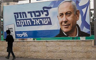 A man walks past an election campaign poster for Benjamin Netanyahu, prime minister and head of the Likud party in Jerusalem on April 2, 2019 (Yonatan Sindel/Flash90)