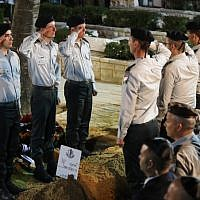 Israeli soldiers salute by the fresh grave of Zachary Baumel, who went missing at the Battle of Sultan Yacoub in 1982, during his funeral at the Mount Herzl Military cemetery in Jerusalem on April 4, 2019. (Hadas Parush/Flash90)