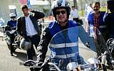Blue and White party leader Benny Gantz rides a motorcycle during a campaign event in Tel Aviv, on April 7, 2019. (Tomer Neuberg/ Flash90)