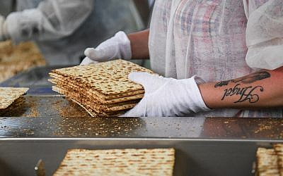 Workers prepare matzah, the unleavened bread eaten during the eight-day Jewish holiday of Passover, in Aviv Matzah plant in Bnei Brak on April 14, 2019 (Courtesy Flash 90)