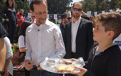 Sixth grade students in Tel Aviv holding a bake sale to raise money for their end of year party show off their baked goods to Zehut party candidate Moshe Feiglin outside a voting booth on April 9, 2019. Feiglin did not support the bake sale. (Melanie Lidman/Times of Israel)