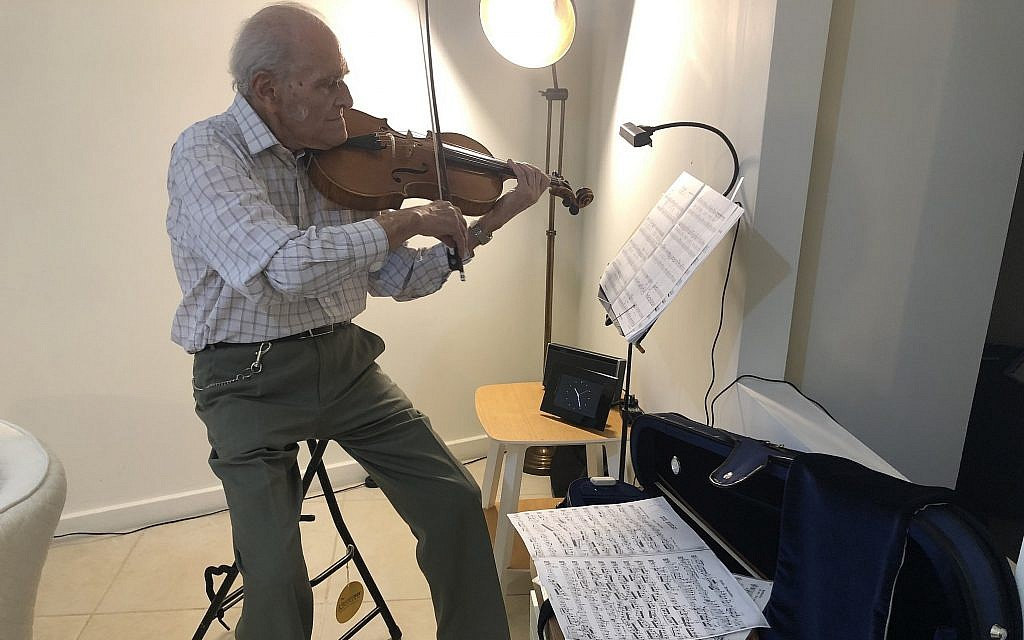 Nonagenarian Eric Sargon, who played for The Beatles, Eric Clapton and the BBC Orchestra, plays his viola in his new Jerusalem apartment (Jessica Steinberg/Times of Israel)