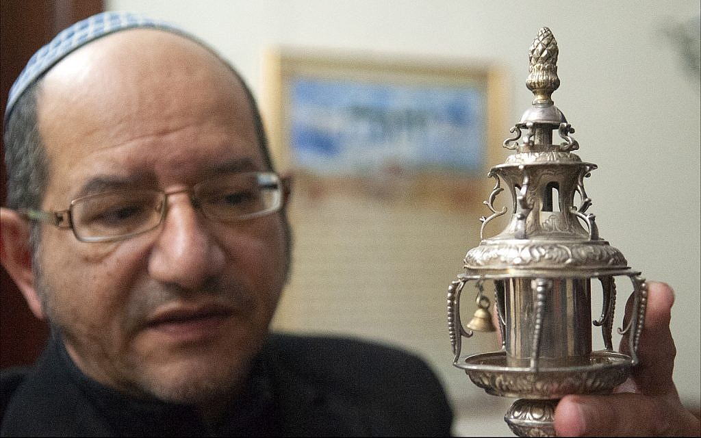 Reuven Ohayon, longtime leader of Malta's tiny Jewish community, displays a silver ornament crowning a Libyan Torah scroll at the synagogue in Ta'Xbiex. (Larry Luxner/Times of Israel)