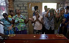 Relatives weep near the coffin with the remains of 12-year Sneha Savindi, who was a victim of Easter Sunday bombing at St. Sebastian Church, April 22, 2019 in Negombo, Sri Lanka. (AP Photo/Gemunu Amarasinghe)