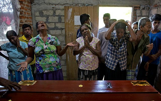 Relatives weep near the coffin with the remains of 12-year Sneha Savindi, who was a victim of Easter Sunday bombing at St. Sebastian Church, April 22, 2019 in Negombo, Sri Lanka. (AP Photo/Gemunu Amarasinghe)