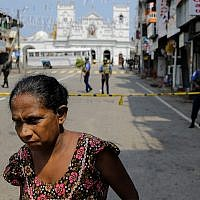 A Sri Lankan woman walks on a road leading to St. Anthony's Church, one of the sites of Easter Sunday's bomb attacks in Colombo, Sri Lanka, April 25, 2019. (AP Photo/Eranga Jayawardena)