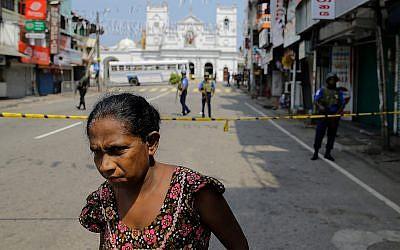 A Sri Lankan woman walks on a road leading to St. Anthony's Church, one of the sites of Easter Sunday's bomb attacks in Colombo, Sri Lanka, April 25, 2019. (AP/Eranga Jayawardena)