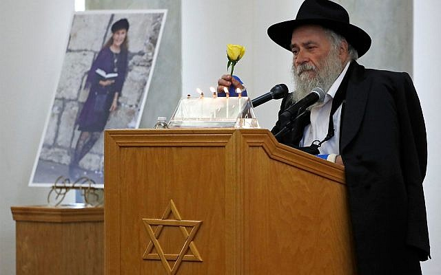 Yishoel Goldstein, Rabbi of Chabad of Poway, holds a yellow rose as he speaks Monday, April 29, 2019, at the funeral for Lori Gilbert-Kaye, who is pictured at left, in Poway, California. (AP Photo/Gregory Bull)