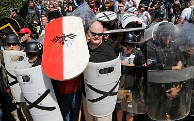 White nationalist demonstrators use shields to guard the entrance to Lee Park in Charlottesville, Virginia, August 12, 2017. (AP Photo/Steve Helber, File)