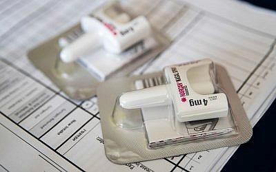 A Narcan nasal device which delivers naloxone lies on a counter as a health educator gives instructions on how to administer it in Brooklyn, New York, July 3, 2018. (AP Photo/Mary Altaffer)