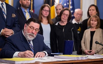 Pittsburgh Mayor Bill Peduto, surrounded by supporters and family members of Tree of Life synagogue shooting victims, signs three gun-control bills into law, April 9, 2019, at the City-County Building in downtown Pittsburgh. (Steph Chambers/Pittsburgh Post-Gazette via AP)