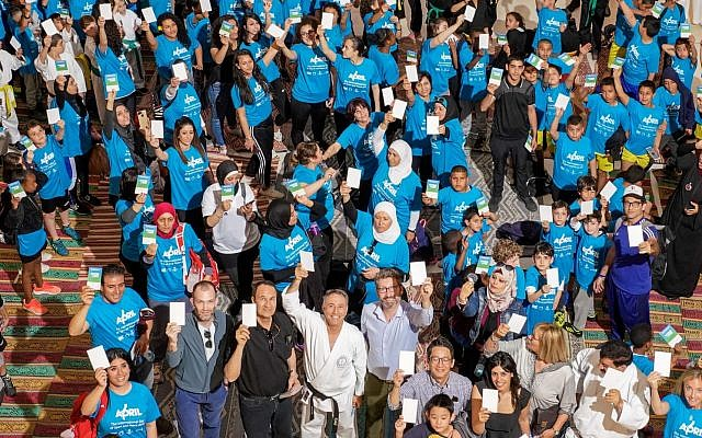 "Participants in the 'White Card Day' event -- the global United Nations ""International Day of Sport for Development and Peace"" -- held in Israel for the first time on April 7, 2019, hold up their white cards. (Jordan Polevoy)"