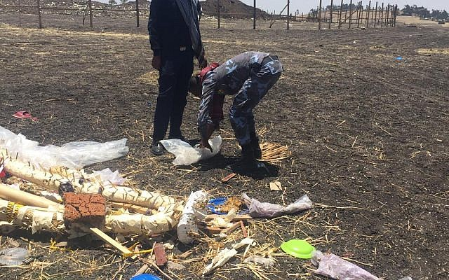 Workers use discarded plastic to pick up debris from the scene where an Ethiopian Airlines Boeing 737 crashed shortly after takeoff last month, killing all 157 on board, near Bishoftu, Ethiopia in April 2019. (Courtesy)