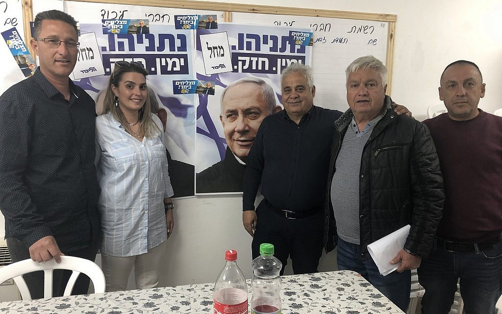 Benny Biton, mayor of Dimona (third from right), poses with fellow Likud activists at the Likud party's campaign headquarters, Dimona, April 8, 2019. (Sue Surkes/Times of Israel.)