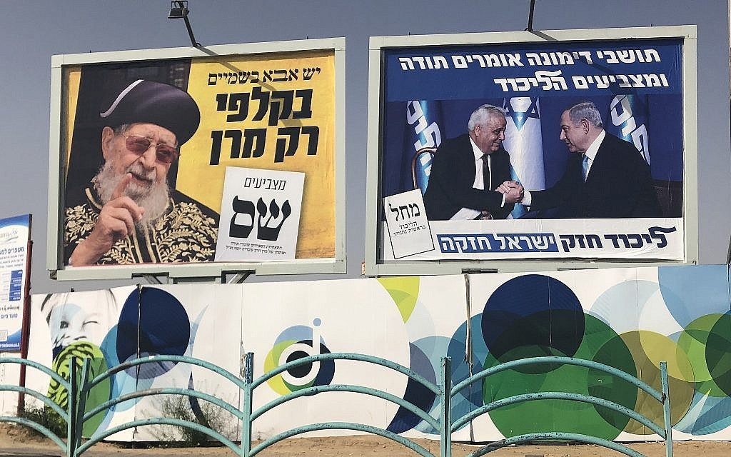 Campaign posters for the Likud party (right), featuring Dimona mayor Benny Biton with Prime  Minister Benjamin Netanyahu, and for the ultra-Orthodox Shas party, seen in the Negev city of Dimona, April 8, 2019. (Sue Surkes/Times of Israel)