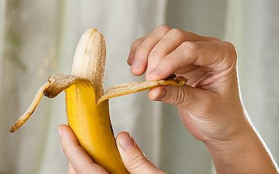 Illustrative photo of a person peeling a banana. (iStock)