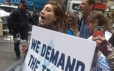 An activist with IfNotNow protests outside the offices of Birthright Israel in New York City on Friday, April 5, 2019. (Ben Sales)