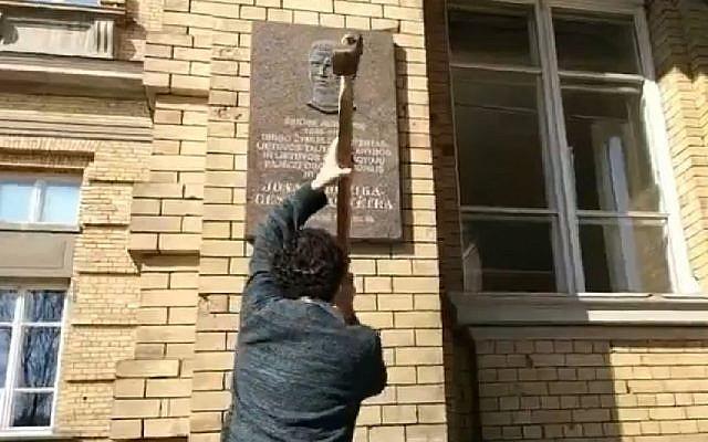 Stanislovas Tomas smashes the plaque honoring Jonas Noreika in Vilnius, Lithuania, April 7, 2019 (Screen grab via Facebook)