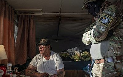 Larry Hopkins, seated, also known as Striker, the leader of the United Constitutional Patriots New Mexico Border Ops militia, inside the team's camper near the US-Mexico border in Anapra, New Mexico, March 20, 2019. (Paul Ratje/AFP/Getty Images via JTA)