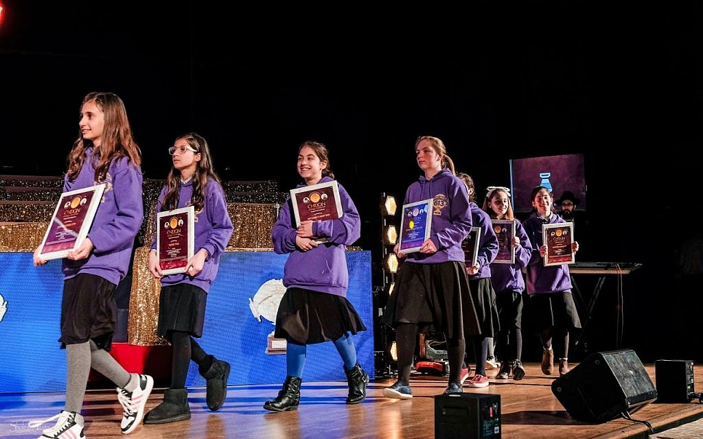 Girls coming onstage at the 5th annual Chidon Sefer Hamitzvos Girls' Tournament in Newark, New Jersey, March 31, 2019. (Courtesy Chabad/Sholem Photography)
