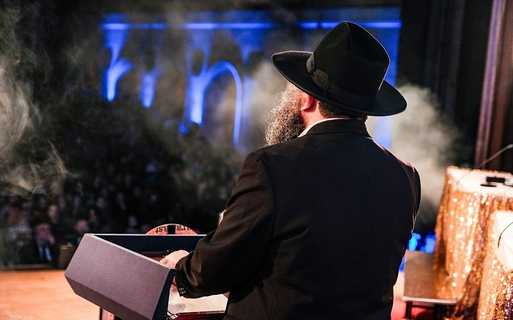 A rabbi speaking onstage at the 5th annual Chidon Sefer Hamitzvos Girls' Tournament in Newark, New Jersey, March 31, 2019. (Courtesy Chabad/Sholem Photography)