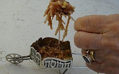 Passover delicacy haroset being spooned into a small silver wagon, used by some Jews to serve the dish. (The Toby Press)