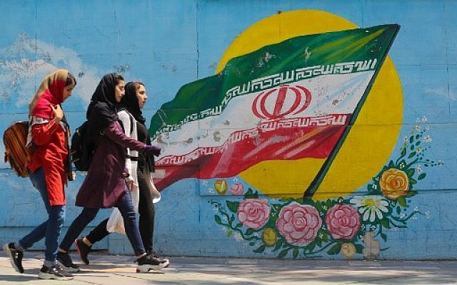Young girls walk in front of a mural showing the Iranian national flag in the center of the  capital Tehran, April 23, 2019. (ATTA KENARE / AFP)