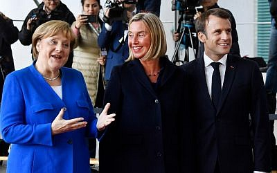 German Chancellor Angela Merkel (L) and French President Emmanuel Macron (R) greet EU's High representative for foreign affairs and security policy Federica Mogherini (C) as she arives at the chancellery in Berlin on April 29, 2019 for the West Balkans conference (John MACDOUGALL / AFP)