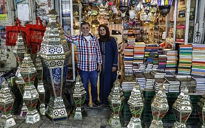 Palestinian craftsman Issam Zughair stands with his wife next to an assortment of Ramadan lanterns in the entrance of his shop in the Old City of Jerusalem on May 2, 2019 (AHMAD GHARABLI / AFP)
