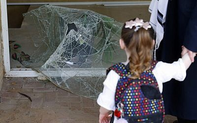 An Israeli child on May 6, 2019, looks at shattered glass at the entrance to a building damaged by a rocket strike from the Gaza Strip, in the southern Israeli city of Ashdod. (Jack Guez/AFP)