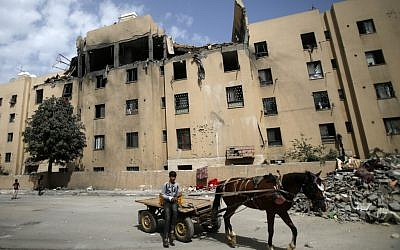 A young Palestinian rides a horse-drawn cart on May 6, 2019, in front of a building that was damaged during an Israeli airstike on Beit Lahia in the northern Gaza Strip. (MOHAMMED ABED / AFP)