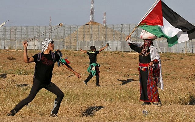 A protester hurls stones at Israeli troops as a woman wearing a traditional Palestinian outfit waves a national flag, during a demonstration near the border with Israel, east of Gaza City, on May 10, 2019. (Said KHATIB / AFP)
