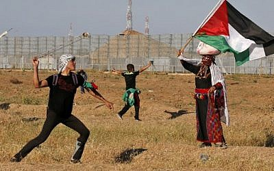 A Palestinian rioter hurls stones at Israeli troops as a woman wearing a traditional Palestinian outfit waves a national flag near the border with Israel, east of Gaza City, on May 10, 2019. (Photo by Said KHATIB / AFP)