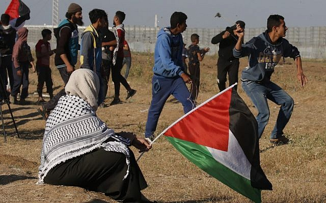 A protester hurls stones at Israeli troops as a woman holds a Palestinian national flag, during a demonstration near the border with Israel, east of Gaza City, on May 10, 2019. (Said KHATIB / AFP)