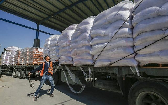 A Palestinian worker checks a truck carrying United Nations Relief and Work Agency (UNRWA) aid supplies that arrived through the Kerem Shalom crossing from Israel to the southern Gaza Strip city of Rafah on May 12, 2019. (SAID KHATIB/AFP)