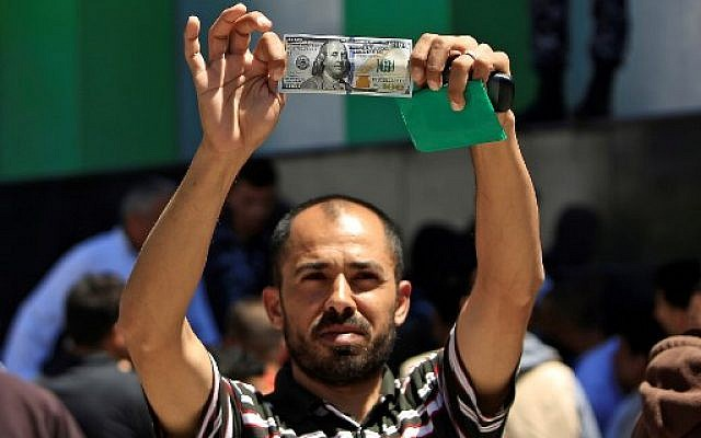 A Palestinian man displays a 100 dollar bill, part of $480 million in aid allocated by Qatar, in Gaza City on May 13, 2019.  (MOHAMMED ABED / AFP)