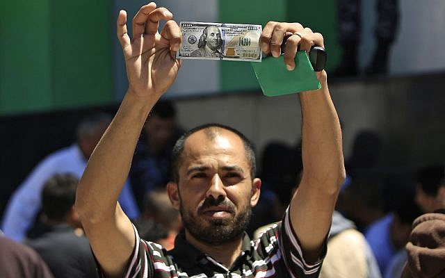 A Palestinian man holds a $100 bill, part of $480 million in aid allocated by Qatar, in Gaza City on May 13, 2019. (MOHAMMED ABED / AFP)