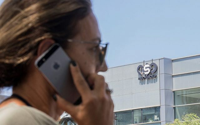 An Israeli woman uses her phone in front of a building in Herzliya that housed the NSO Group intelligence firm, August 28, 2016. (Jack Guez/AFP/File)