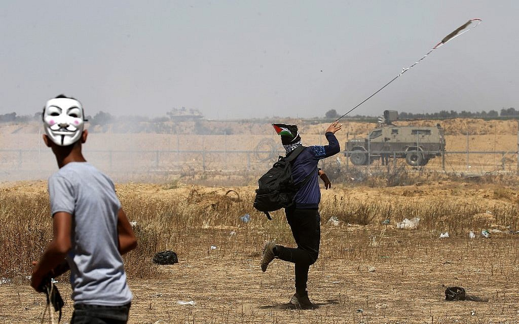 Palestinian demonstrators hurl rocks towards Israeli soldiers east of Khan Yunis in the southern Gaza Strip on May 15, 2019, during a protest marking 71th anniversary of Nakba (Said KHATIB / AFP)