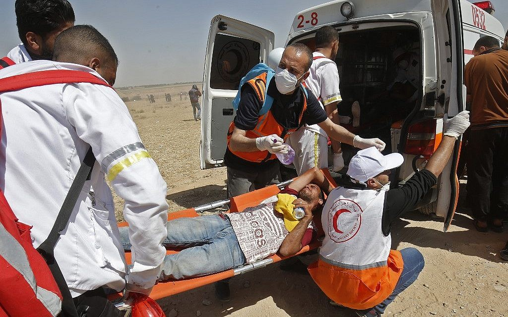 Palestinian medics carry a wounded demonstrator east of Khan Yunis in the southern Gaza Strip on May 15, 2019, during a Nakba protest. (Said KHATIB / AFP)