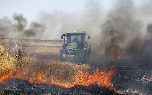 Illustrative: An Israeli farmer uses a tractor in an attempt to extinguish a fire in a wheat field near the Kibbutz Nahal Oz, along the border with the Gaza Strip, on May 15, 2019 after it was caused by inflammable material attached to helium balloon flown by Palestinian protesters from across the border (Menahem KAHANA / AFP)