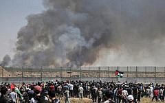 Palestinian protestors riot along the security fence east of Gaza City as smoke billows from fields across the fence  caused by an incendiary device attached to a kite and flown across the border into Israel from the Gaza Strip, on May 15, 2019. (MAHMUD HAMS / AFP)