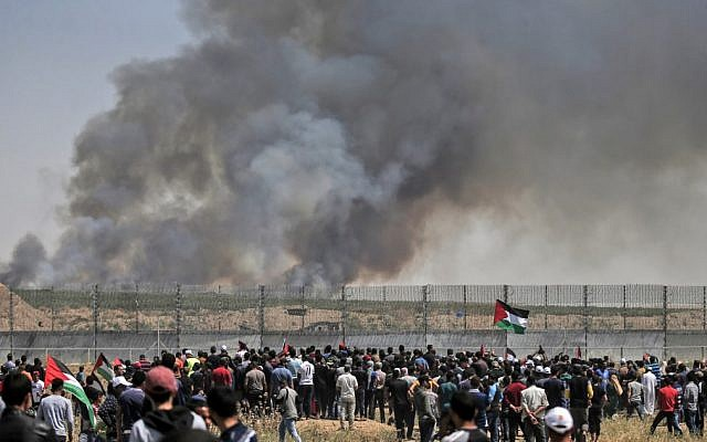 Palestinian protesters riot along the security fence east of Gaza City as smoke billows from fields across the fence caused by an incendiary device attached to a kite and flown across the border into Israel from the Gaza Strip, on May 15, 2019. (MAHMUD HAMS / AFP)