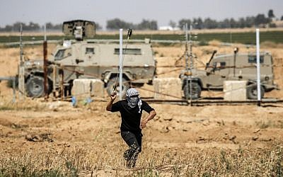 A Palestinian rioter uses a slingshot to hurl a rock at Israeli troops during Nakba Day protests east of Khan Younis in the southern Gaza Strip on May 15, 2019. (Thomas COEX / AFP)