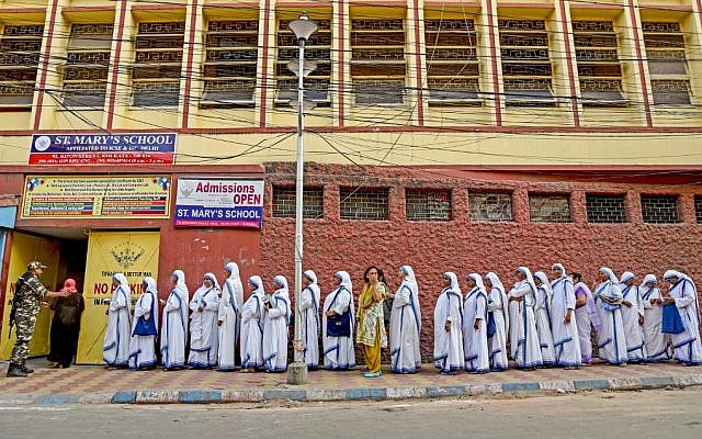 Indian nuns from the Mother Teresa Missionaries of Charities queue to cast their votes as a paramilitary force personnel stands guard at a polling station at St. Mary's School in Kolkata on May 19, 2019, during the 7th and final phase of India's general election. (Amit Datta / AFP)