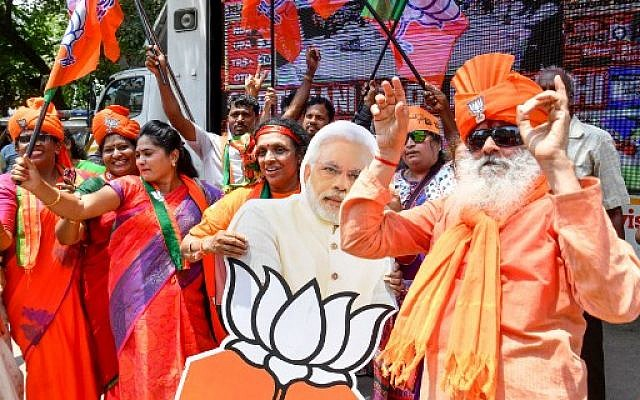 Indian supporters and party workers of the Bharatiya Janata Party (BJP) in Bangalore dance and hold flags as they celebrate the results of India's general election on May 23, 2019. (Manjunath Kiran/AFP)