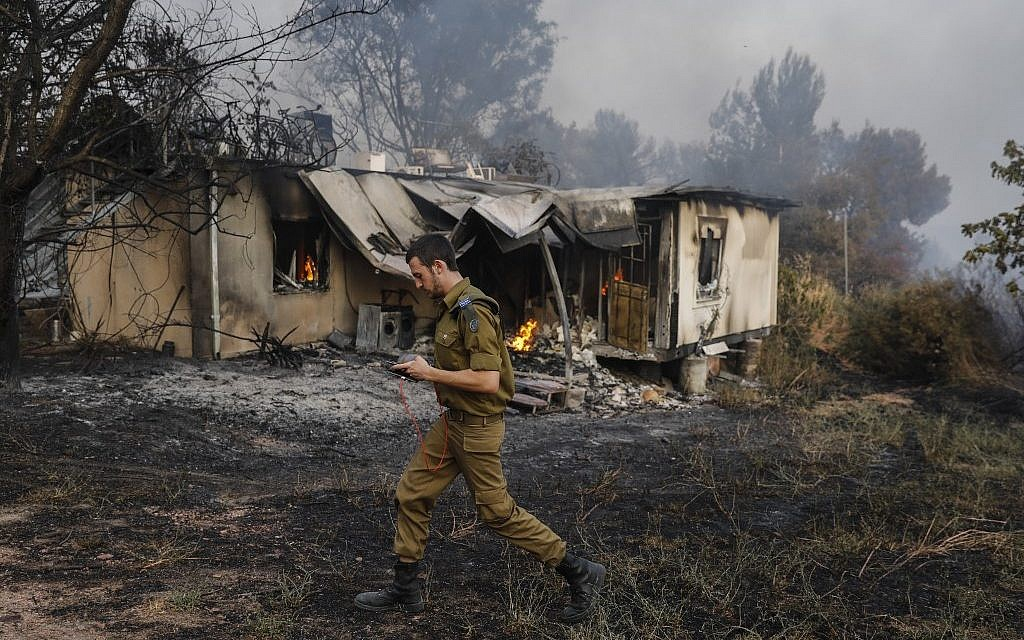 An Israeli soldier walks past a burning house amid extreme heat wave in Kibbutz Harel in central Israel on May 23, 2019. (Ahmad GHARABLI / AFP)